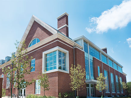 3 story red brick building with large glass windows
